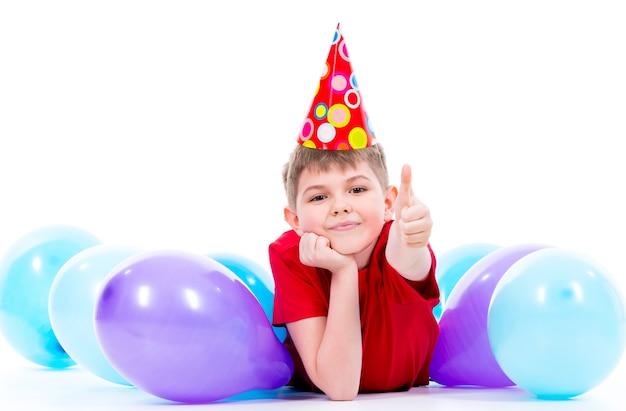 Szczęśliwy uśmiechnięty chłopiec w czerwonej koszulce leżącej na podłodze z kolorowych balonów i pokazujący kciuki do góry - na białym tle.