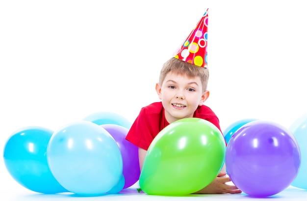 Szczęśliwy uśmiechnięty chłopiec w czerwonej koszulce leżącej na podłodze z kolorowych balonów - na białym tle