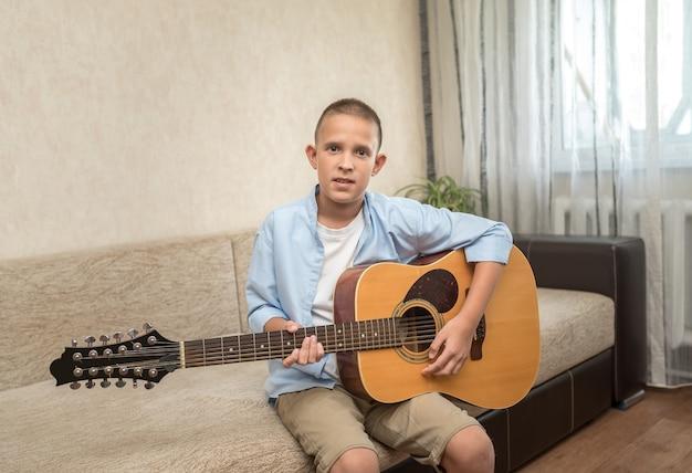 Szczęśliwy uśmiechnięty chłopiec w niebieskiej koszuli uczy się gry na gitarze akustycznej.
