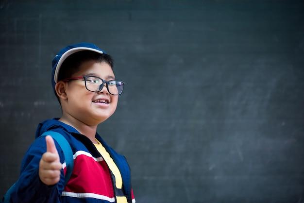 Szczęśliwy uśmiechnięty chłopiec w okularach z kciukiem do góry idzie do szkoły po raz pierwszy.