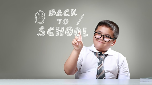 Szczęśliwy uśmiechnięty chłopiec w okularach z koncepcją powrotu do szkoły, chłopiec wskazując z powrotem do szkoły