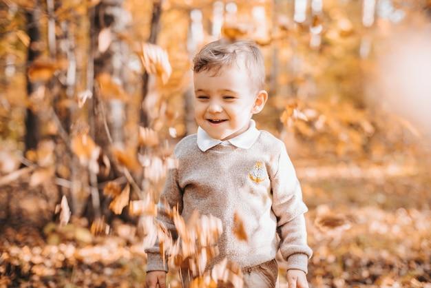 Szczęśliwy uśmiechnięty chłopiec w parku z jesiennych liści