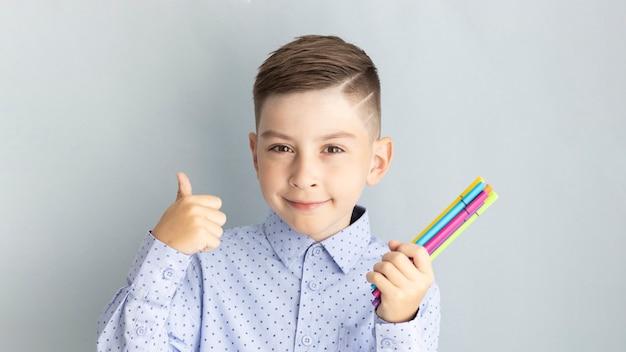 Szczęśliwy uśmiechnięty chłopiec z kciukiem do góry