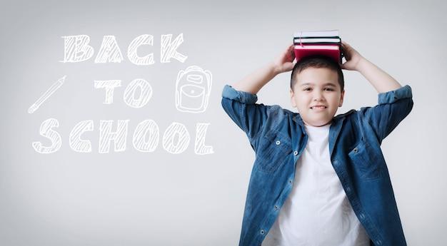 Szczęśliwy uśmiechnięty chłopiec z koncepcją powrotu do szkoły