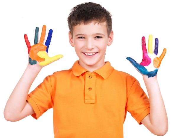 Szczęśliwy uśmiechnięty chłopiec z malowanymi rękami na białym tle.
