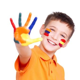 Szczęśliwy uśmiechnięty chłopiec z pomalowaną ręką i twarzą w pomarańczowej koszulce na białym tle.