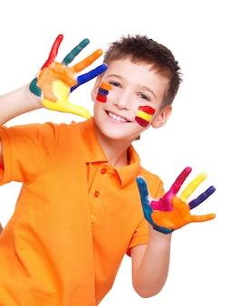 Szczęśliwy uśmiechnięty chłopiec z pomalowanymi rękami i twarzą w pomarańczowej koszulce na białym tle.