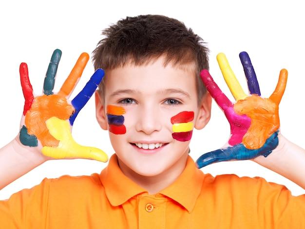 Szczęśliwy uśmiechnięty chłopiec z pomalowanymi rękami i twarzą w pomarańczowej koszulce - na białym tle.