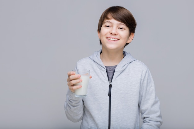 Szczęśliwy uśmiechnięty chłopiec ze szklanką mleka w dłoniach nastolatek na szarym tle
