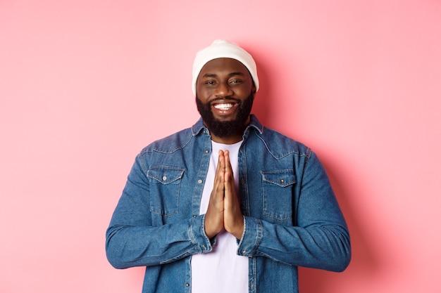 Szczęśliwy uśmiechnięty czarny mężczyzna mówiący dziękuję, trzymający się za ręce w geście modlitwy lub namaste, stojący wdzięczny na różowym tle