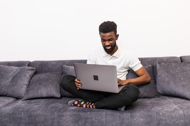 Szczęśliwy uśmiechnięty człowiek afryki oglądania i pracy na komputerze laptop w domu