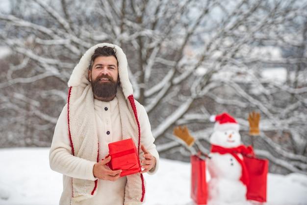 Szczęśliwy uśmiechnięty człowiek śniegu w słoneczny zimowy dzień z szczęśliwym ojcem. ładny mały bałwan i brodaty mężczyzna