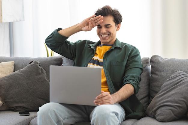 Szczęśliwy uśmiechnięty głuchy młody mężczyzna rasy kaukaskiej używa języka migowego podczas rozmowy wideo za pomocą laptopa, siedząc na kanapie w domu
