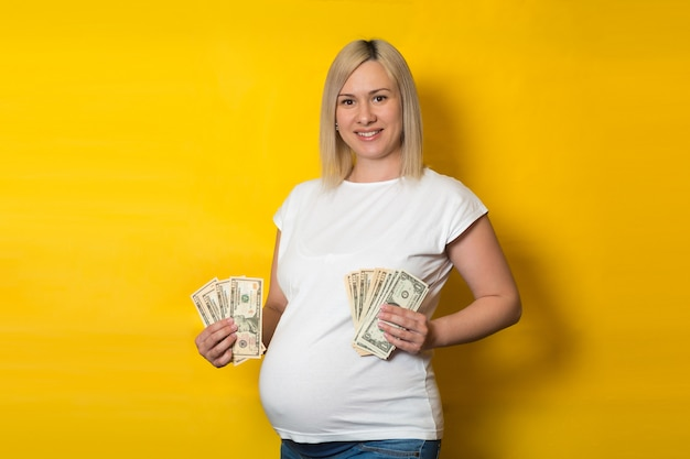 Szczęśliwy uśmiechnięty kobieta w ciąży z pieniądze, dolary na żółtej ścianie. korzyści dla kobiet w ciąży