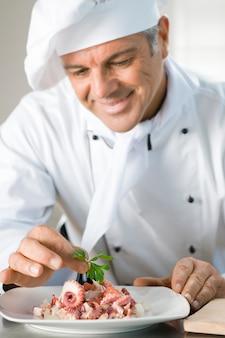Szczęśliwy uśmiechnięty kucharz przyozdabia sałatkę z ośmiornicy liściem persil w restauracji