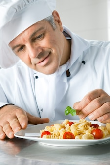 Szczęśliwy uśmiechnięty kucharz udekoruje włoską danie z makaronu liśćmi bazylii