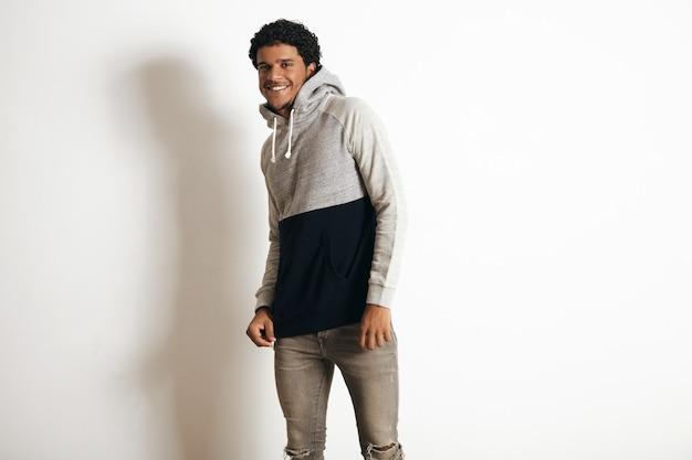 Szczęśliwy uśmiechnięty latynoski facet nosi pusty szary czarny sweter z kapturem i dżinsy w trudnej sytuacji, na białym tle