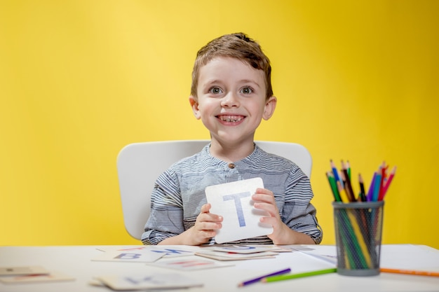 Szczęśliwy uśmiechnięty mały chłopiec w wieku przedszkolnym pokazuje listy w domu odrabiania lekcji rano przed rozpoczęciem szkoły. nauka angielskiego dla dzieci.