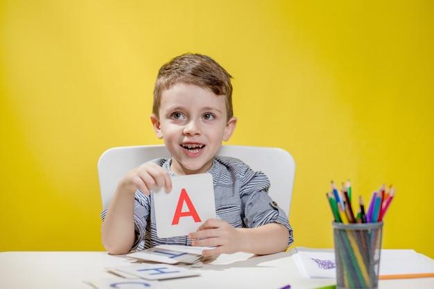 Szczęśliwy uśmiechnięty mały chłopiec w wieku przedszkolnym pokazuje listy w domu odrabiania lekcji rano przed rozpoczęciem szkoły