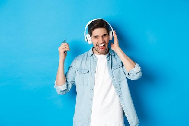 Szczęśliwy uśmiechnięty mężczyzna cieszący się słuchaniem muzyki w słuchawkach, trzymający smartfon w podniesionej dłoni, stojący na niebieskim tle