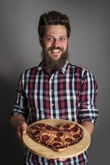 Szczęśliwy uśmiechnięty mężczyzna daje pizzę w kształcie spalonego serca