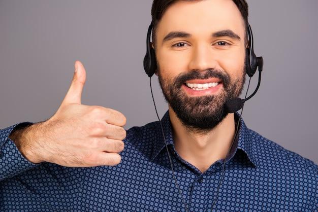 Szczęśliwy uśmiechnięty mężczyzna gestykuluje w słuchawkach