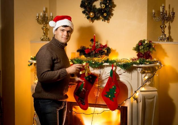 Szczęśliwy uśmiechnięty mężczyzna pozuje z pudełkiem prezentowym przy ozdobionym kominku