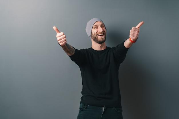 Szczęśliwy uśmiechnięty mężczyzna trzyma kciuki na szaro.