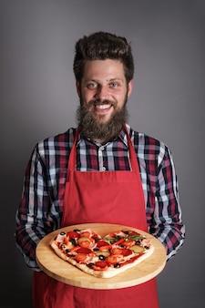 Szczęśliwy uśmiechnięty mężczyzna trzymający pizzę domowej roboty w kształcie serca