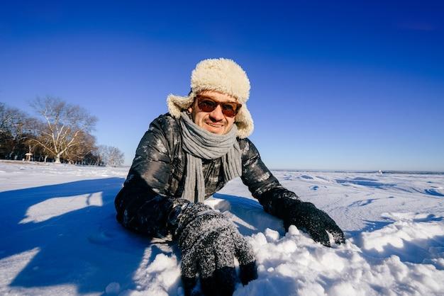 Szczęśliwy uśmiechnięty mężczyzna w okularach przeciwsłonecznych, stwarzających w śniegu na zewnątrz