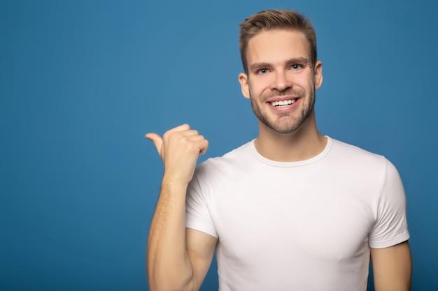 Szczęśliwy uśmiechnięty mężczyzna wskazuje z palcem backwards odizolowywającym na błękicie