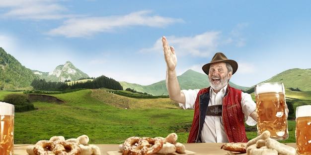 Szczęśliwy Uśmiechnięty Mężczyzna Z Piwem Ubrany W Tradycyjny Austriacki Lub Bawarski Strój Premium Zdjęcia