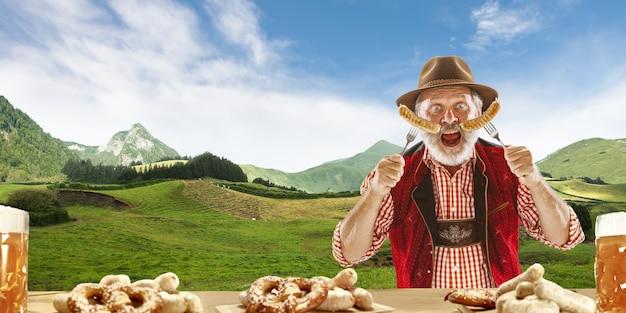 Szczęśliwy uśmiechnięty mężczyzna z piwem ubrany w tradycyjny austriacki lub bawarski strój