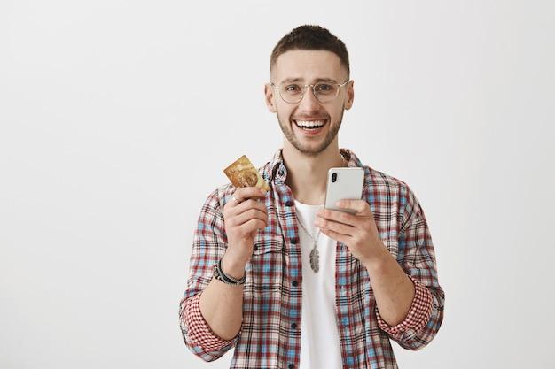 Szczęśliwy uśmiechnięty młody chłopak w okularach z jego telefonem i kartą