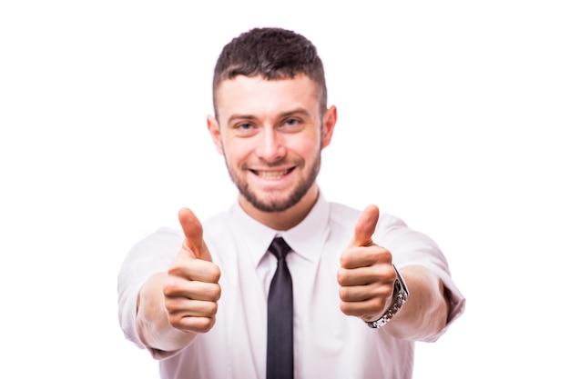 Szczęśliwy uśmiechnięty młody człowiek biznesu z kciuki do góry gest, na białym tle nad białą ścianą
