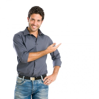 Szczęśliwy uśmiechnięty młody człowiek, prezentując i pokazując twój tekst lub produkt na białym tle