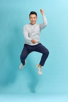 Szczęśliwy uśmiechnięty młody człowiek skoki