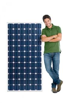 Szczęśliwy uśmiechnięty młody człowiek stojący z panelem słonecznym na energię odnawialną, na białym tle