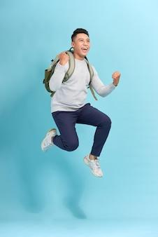 Szczęśliwy uśmiechnięty młody człowiek z plecakiem, skoki