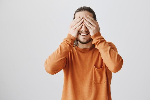 Szczęśliwy uśmiechnięty młody człowiek zamyka oczy i czeka na niespodziankę