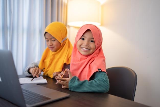Szczęśliwy uśmiechnięty młody muzułmański dzieciak z laptopem razem patrzący na kamerę