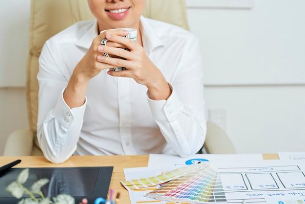 Szczęśliwy uśmiechnięty młody niezależny grafik siedzący w domu przy biurku i pijący z kubka morni...
