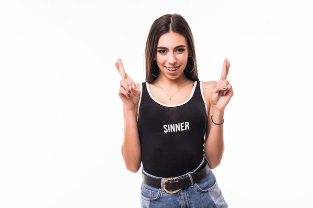 Szczęśliwy uśmiechnięty model z nawiasami klamrowymi pokazuje crossfingers znaka na obu rękach odizolowywać