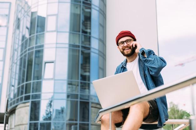 Szczęśliwy uśmiechnięty nowożytny młody pomyślny freelancer siedzi w mieście, pracuje na laptopie i dzieli się dobre wieści z klientem na telefonie o postępie w projekcie.