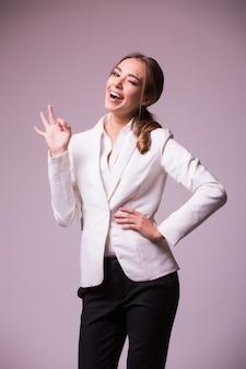 Szczęśliwy uśmiechnięty piękny młody bizneswoman pokazuje dobry gest, na szarej ścianie. kaukaski blond model w koncepcji prezentacji biznesowych. kwadratowa kompozycja.