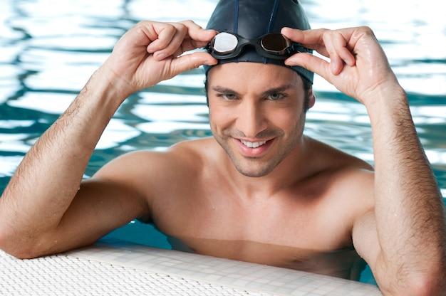 Szczęśliwy uśmiechnięty pływak lekkoatletyczny w okularach w basenie