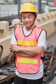 Szczęśliwy uśmiechnięty pracownik budowlany stojący ze stosem surowca