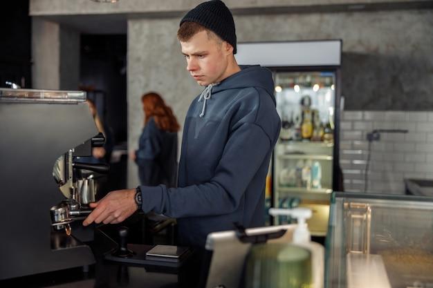 Szczęśliwy uśmiechnięty profesjonalny barista w kawiarni
