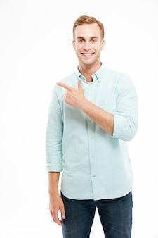 Szczęśliwy uśmiechnięty przypadkowy mężczyzna wskazujący palcem na copyspace na białej ścianie