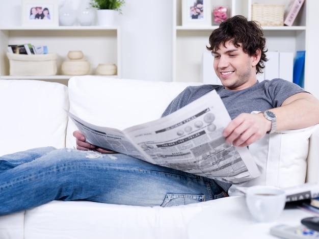 Szczęśliwy uśmiechnięty przystojny mężczyzna czyta gazetę w domu
